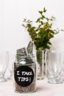 Ich nehme ein mit geld gefülltes trinkglas und pflanze im hintergrund