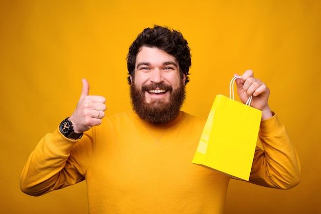 Ich schätze die möglichkeit zum online-shopping. lächelnder mann zeigt daumen hoch und gelbe papiertüte.