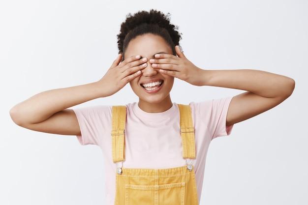 Ich sehe keine probleme und lass es mich wissen, wenn ich herauskomme. porträt eines charmanten und sorglosen afroamerikaners in gelben overalls, die augen mit den handflächen schließen und breit lächeln, auf überraschungsgeschenk wartend