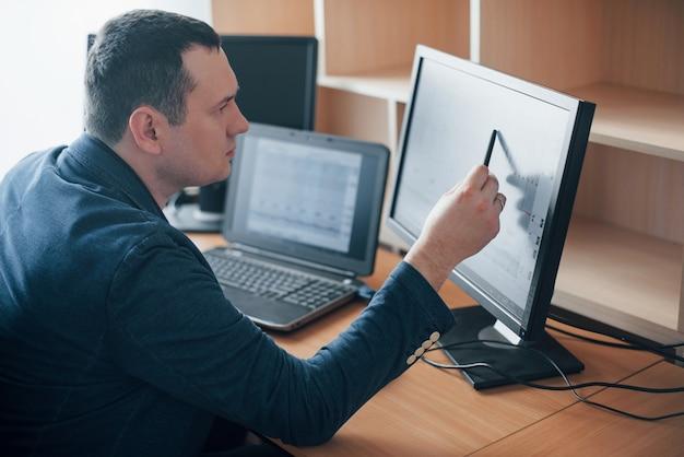 Ich sehe, wie sehr sich der mensch in diesem moment sorgen gemacht hatte. der polygraph-prüfer arbeitet im büro mit der ausrüstung seines lügendetektors