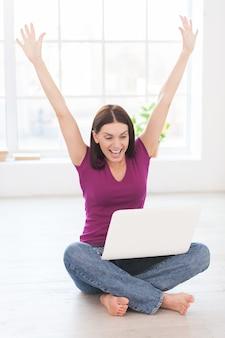 Ich tat es! glückliche junge frau, die die arme erhoben hält und positivität ausdrückt, während sie am laptop in ihrer wohnung arbeitet