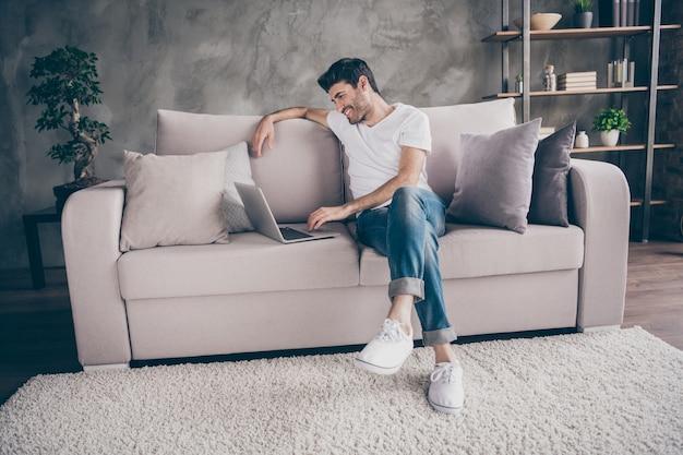 Ich vermisse dich so sehr! profilfoto des kerles der gemischten rasse, der gemütliches sofa sitzt, das notebook sprechendes skype mit verwandten kommuniziert, tragen tragen lässiges outfit flaches loft-wohnzimmer drinnen