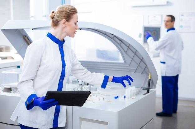 Ich verstehe es. gut aussehende neugierige laborassistentin, die glaswaren nehmen möchte, während sie eine tablette hält und posiert