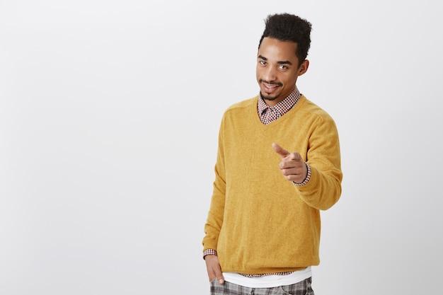 Ich wähle dich, um mit mir zu arbeiten. porträt des attraktiven amerikanischen männlichen modells mit afro-haarschnitt im gelben pullover, der mit selbstbewusstem und charmantem ausdruck zeigt und flirtet