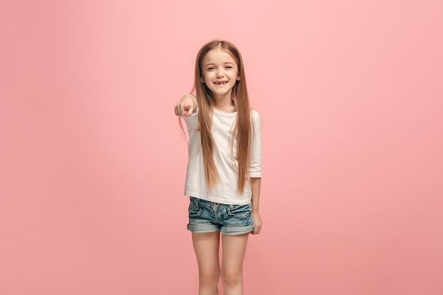 Ich wähle dich und bestelle. das lächelnde jugendlich mädchen, das auf kamera zeigt, halbes länge nahaufnahmeporträt auf rosa