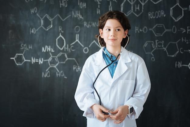 Ich wähle meinen zukünftigen beruf. intelligent involviert charmanter schüler, der in der schule in der nähe der tafel steht, während er unterricht hat und stethoskop benutzt