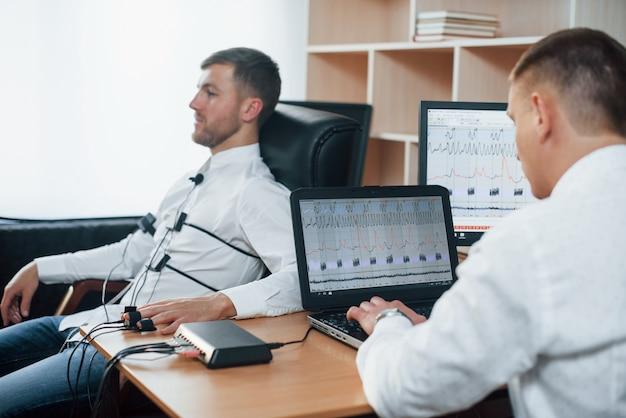 Ich war nicht da verdächtiger mann übergibt lügendetektor im büro. fragen stellen. polygraphentest