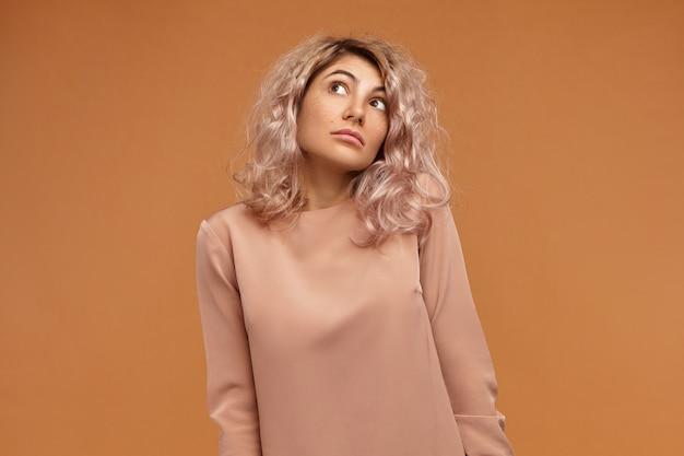 Ich weiß es nicht. ahnungslose emotionale junge europäische frau mit rosa haaren, die mit großen augen nach oben schauen