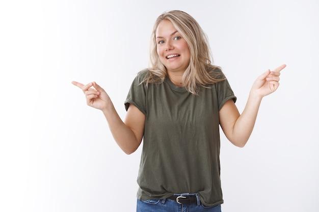 Ich weiß es nicht, entscheide selbst. unsichere und ahnungslose attraktive blonde frau in olivgrünem t-shirt, die ahnungslos mit den schultern zuckt und links rechts seitwärts in verschiedene richtungen zeigt und fragt, welche wahl getroffen werden soll