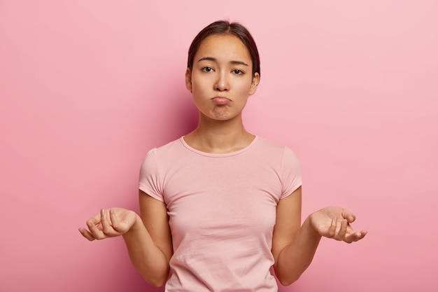 Ich weiß es nicht. unbekannte verblüffte junge asiatische frau breitet die handflächen seitwärts aus, hat keine ahnung, was zu tun ist, trägt ein lässiges t-shirt, sieht traurig aus und überlegt, wie sie sich in einer schwierigen situation verhalten soll
