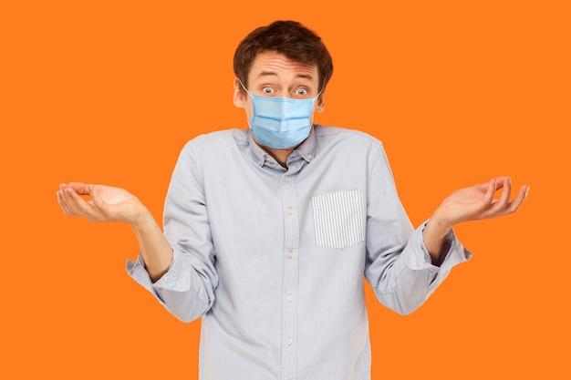 Ich weiß nicht. porträt eines verwirrten jungen arbeitermannes mit chirurgischer medizinischer maske, der die kamera steht und anschaut und fragt. indoor-studioaufnahme auf orangem hintergrund isoliert.