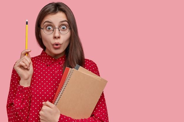 Ich weiß was ich schreiben soll! schöner überraschter schriftsteller hebt hand mit bleistift, trägt lehrbücher, spiralblock, trägt brille