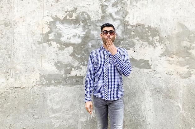 Ich werde leise sein. porträt eines schockierten, gutaussehenden, bärtigen jungen mannes in kariertem blauem hemd und sonnenbrille, der gegen eine graue betonwand steht. schaute mit schockiertem gesicht und schloss den mund.