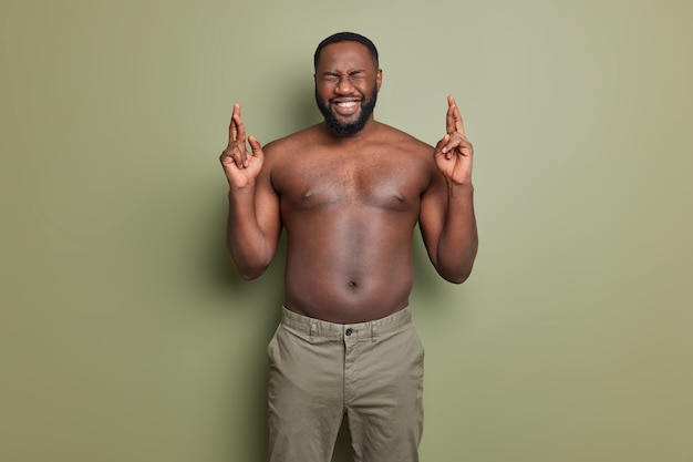 Ich will gewinnen. positiver dunkelhäutiger afroamerikaner drückt die daumen und wünscht sich bessere posen mit nacktem oberkörper