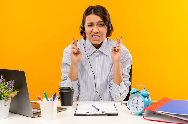 Ich wünsche ein junges callcenter-mädchen, das ein headset trägt, das am schreibtisch mit den werkzeugen sitzt, die finger kreuzen, die auf orange hintergrund lokalisiert werden