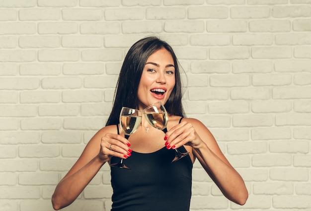 Ich wünsche ihnen ein frohes neues jahr. eine junge und schöne frau tanzt mit einem glas champagner