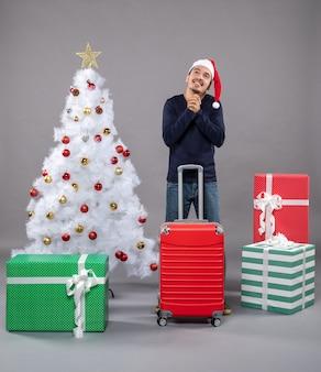 Ich wünsche weihnachtsmann mit weihnachtsmütze in der nähe von weißem weihnachtsbaum mit bunten weihnachtsspielzeugen auf