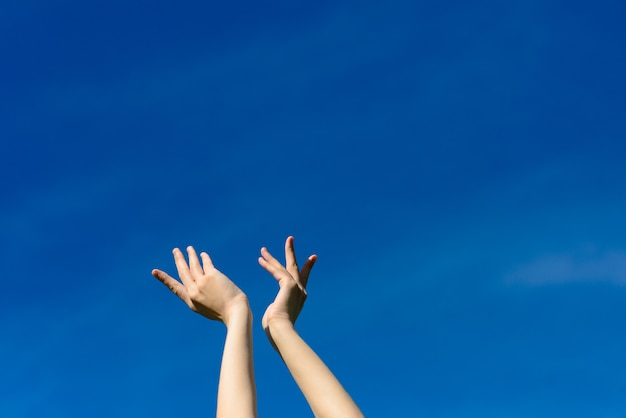 Ich wünschte, wir könnten den himmel berühren, frauen strecken die hände zum blauen himmel. freiheit und frühlingskonzept