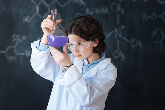 Ich zeige mein wissenschaftliches talent. neugieriger konzentrierter intelligenter junge, der im labor steht und chemieunterricht genießt, während er am wissenschaftsprojekt teilnimmt und die glühbirne erforscht