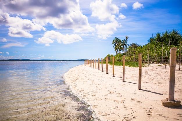 Idealer tropischer strand mit türkisfarbenem wasser und weißem sand auf einer einsamen insel
