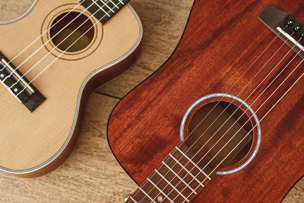 Ideales musikalisches paar. draufsicht auf die nahe beieinander liegenden akustik- und ukulele-gitarren auf dem holzboden. musikinstrumente. musikanlage. musikgeschäft