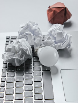 Idee geschäftskonzept. laptop, zerknitterte papierkugeln, led-glühbirne auf grauem tisch
