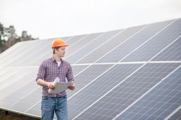 Idee. junger denkender mann in schutzhelm und kariertem hemd mit zeichnung in den händen mit blick auf solarpanel an warmen tagen