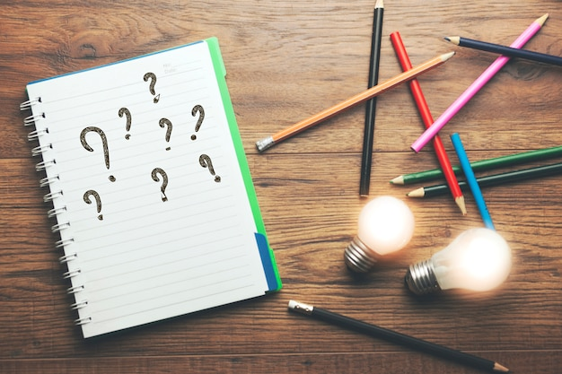 Idee mit fragezeichen auf dem notizbuch mit bleistiften