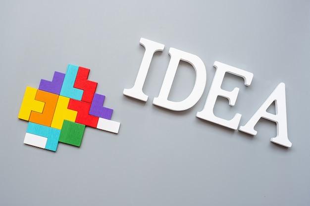 Idee-text mit bunten holzpuzzleteilen auf grau. logisches denken, geschäftslogik, rätsel, inspiration, lösungen, rationalität, mission, erfolg, ziele und strategiekonzepte