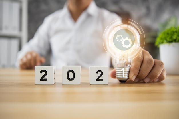 Idee und geschäftsplanung im konzept 2021, geschäftsmann, der glühbirne des innovationsplans mit zahlwürfel auf holztisch hält