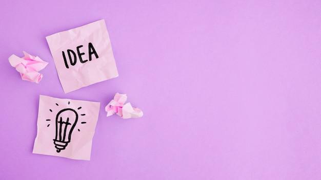 Idee und glühlampe gezeichnet auf zwei klebrigen anmerkungen mit papierball auf purpurrotem hintergrund