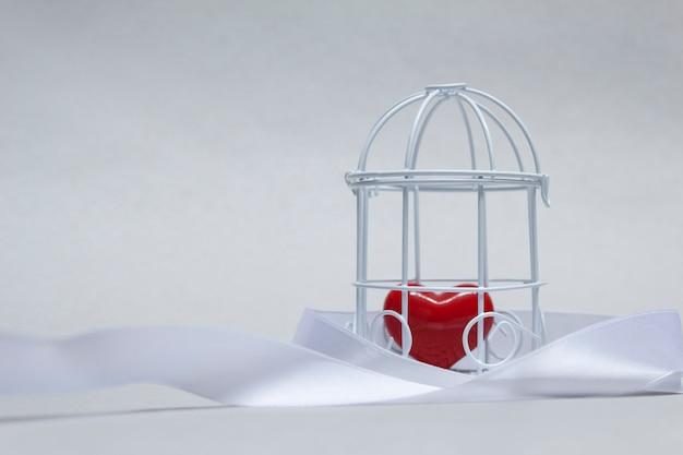 Idee zum thema liebe. dekorative zelle mit einem roten herzen in der gefangenschaft.