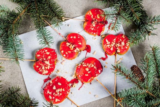 Ideen des winters, weihnachtsleckereien. süßigkeiten für kinder. schokoladen-apfelscheiben in rotem karamell und nüssen. grauer steinhintergrund, mit weihnachtsbaumasten, draufsicht