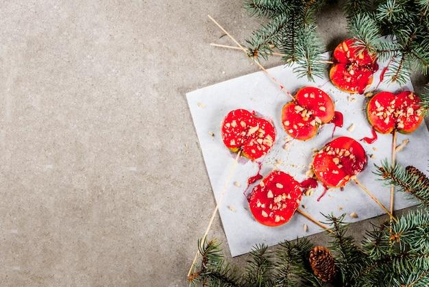 Ideen des winters, weihnachtsleckereien. süßigkeiten für kinder. schokoladen-apfelscheiben in rotem karamell und nüssen. grauer steinhintergrund, mit weihnachtsbaumasten, draufsichtkopienraum