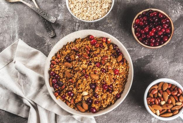 Ideen für ein winter-, herbstfrühstück. das erntedankfest, . selbst gemachtes frisches gekochtes honigmüsli mit nusssalm, erdnüssen, haselnüssen und preiselbeeren. auf grauer konkreter tabelle draufsicht