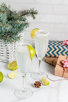 Ideen für weihnachts- und neujahrsgetränke champagner-margarita-cocktails, garniert mit limette und salz