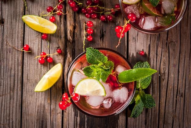 Ideen von sommergetränken, diätetisch gesunden cocktails. mojito aus limette, minze und roten johannisbeeren. ansicht von oben