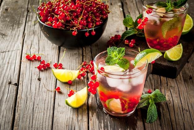 Ideen von sommergetränken, diätetisch gesunden cocktails. mojito aus limette, minze und roten johannisbeeren.