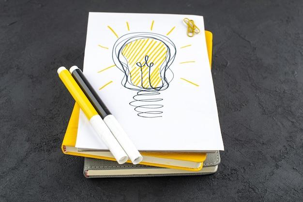 Ideenglühbirne von unten auf notizblock gelbe und schwarze markierungen edelsteinclips auf schwarzem hintergrund
