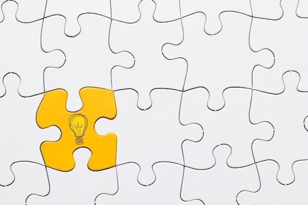 Ideenikone auf gelbem puzzlespielstück schloss an weißen gitterpuzzlespielhintergrund an