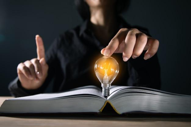 Ideenkonzept, frau mit einer glühbirne eines buches