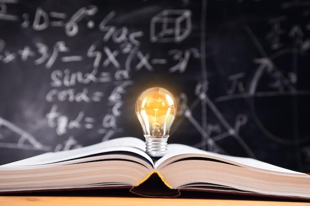 Ideenkonzept, glühbirne auf buch mit tafel