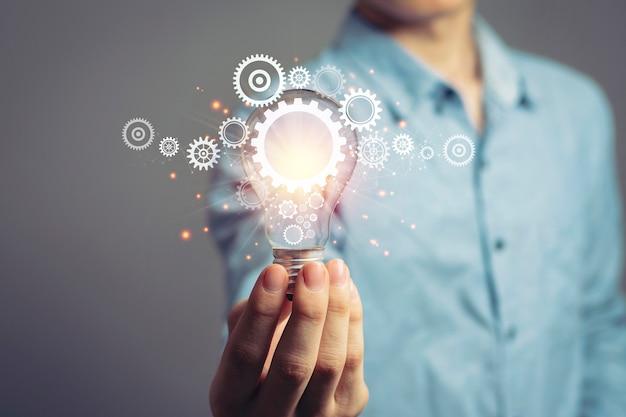 Ideenkonzept und brainstorming-kreativitätsidee denken mit jungem asiatischem geschäftsmann, der glühbirnensymbol hält