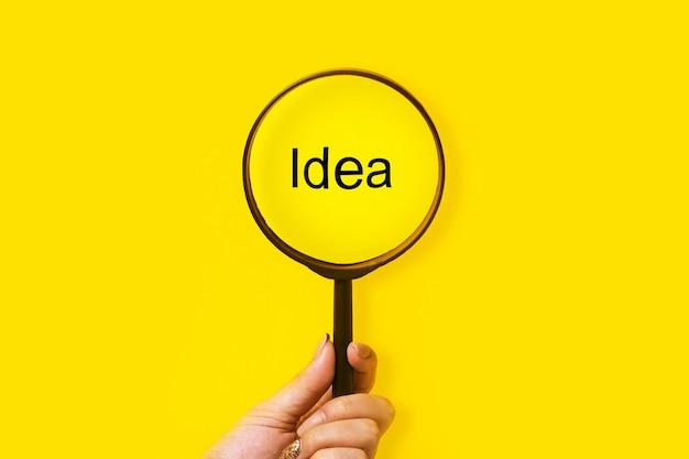 Ideensuche, lupe in der hand über der inschrift