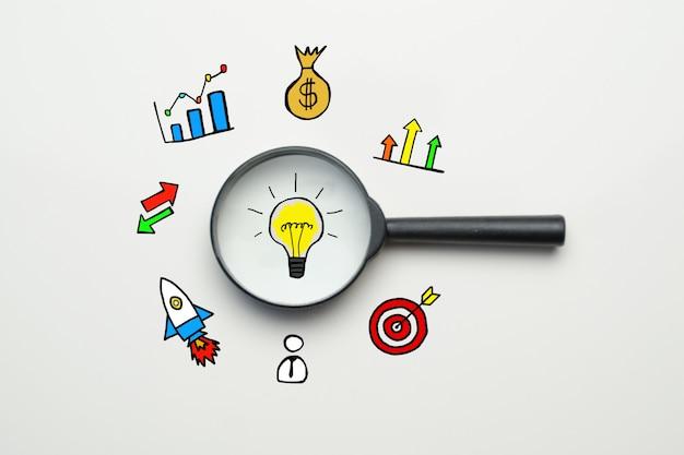 Ideensuchkonzept - lupe mit glühbirne und symbolen.