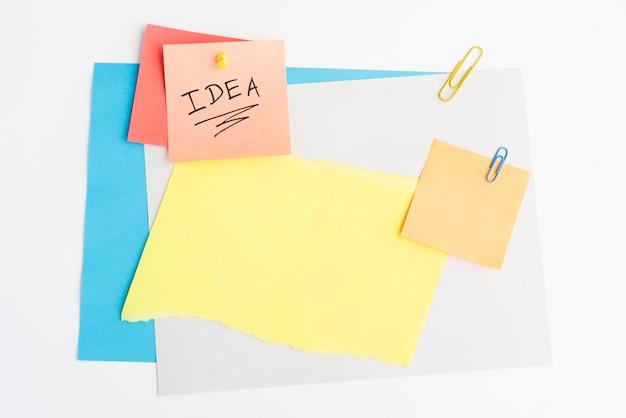 Ideentext geschrieben auf klebrige anmerkung mit druckbolzen und papierklammer auf weißes brett