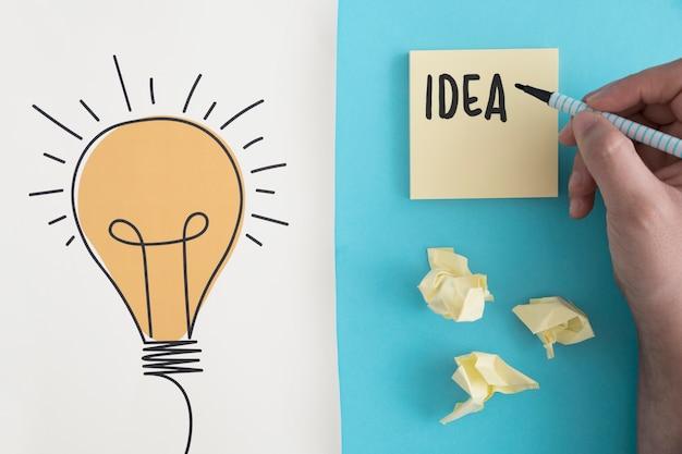 Ideentext geschrieben mit filzstift auf zerknittertes ballpapier mit hand gezeichneter glühlampe