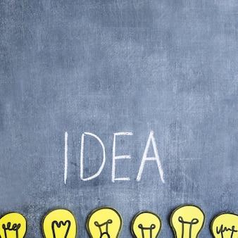 Ideentext geschrieben mit kreide über die reihe von glühlampen des papierausschnitts auf tafel
