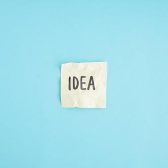 Ideenwort auf dem zerknitterten papier gegen den blauen hintergrund