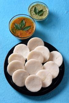 Idli mit sambar- und kokosnusschutney auf blauer oberfläche, indisches gericht: südindisches lieblingsessen rava idli oder grieß untätig oder rava untätig, serviert mit sambar und grünem kokosnusschutney.